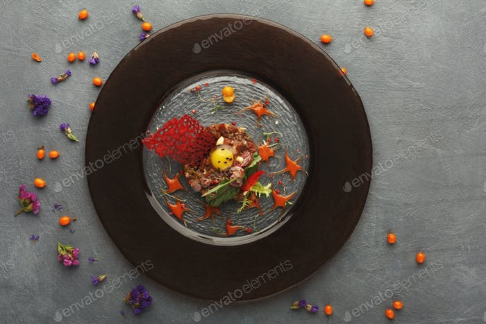 Modern restaurant dish. Veal tartare with quail egg closeup