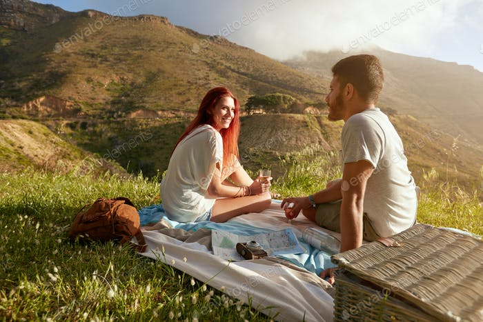 Relaxed couple enjoying romantic picnic in the countryside