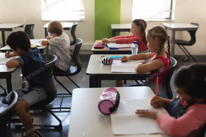 Side view of kids studying in classroom sitting at desks in school