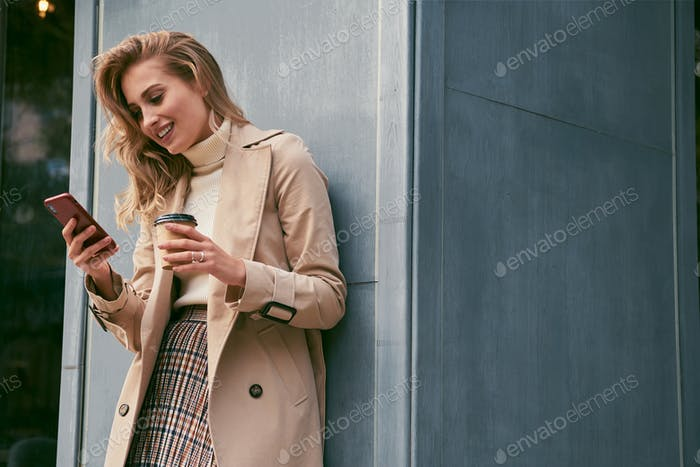 Pretty smiling blond girl in stylish trench coat with coffee to go joyfully using cellphone outdoor
