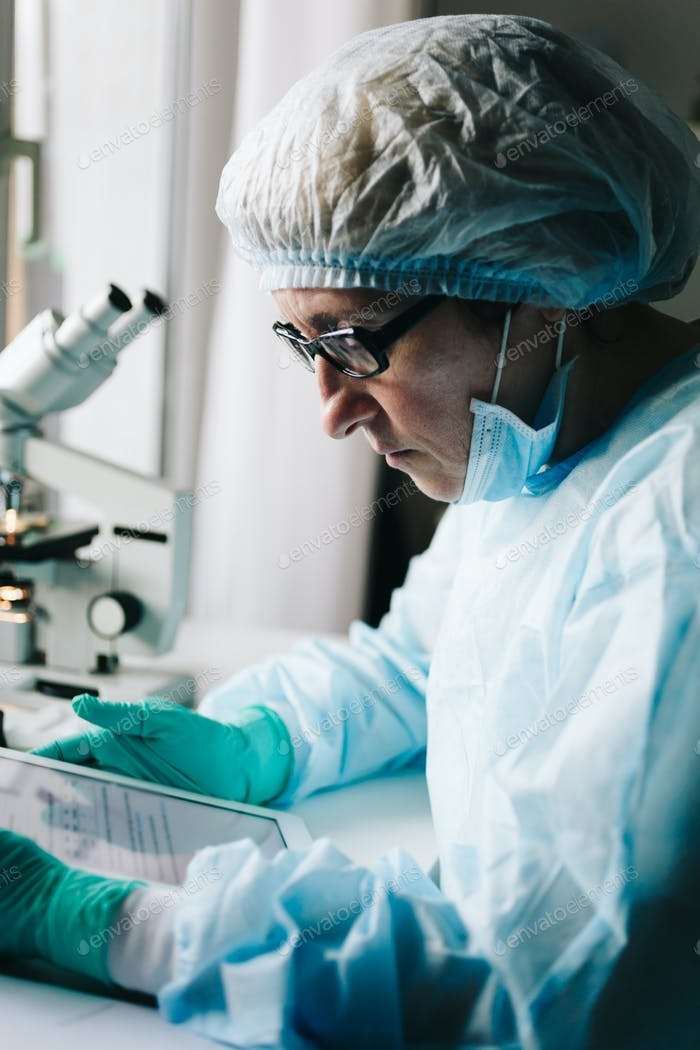 Side view of scientist working on tablet