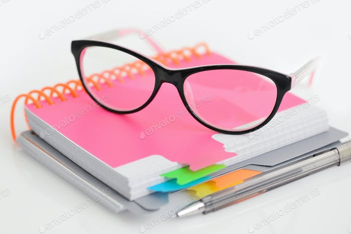 Eye glasses with pen and blank spiral notebook on white backgrou