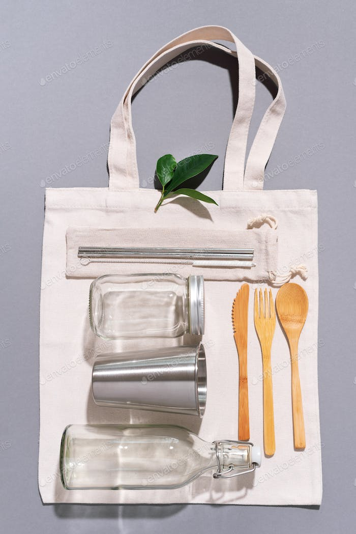 Fabric bags, glass jars, metal straws, bamboo cutlery on grey background with copy space. Eco