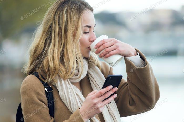 bastante joven mujer bebiendo café mientras el uso de su teléfono móvil