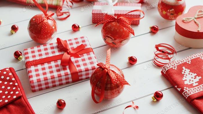 Weihnachtskugeln und Perlen in der Nähe von Weihnachtsgeschenken