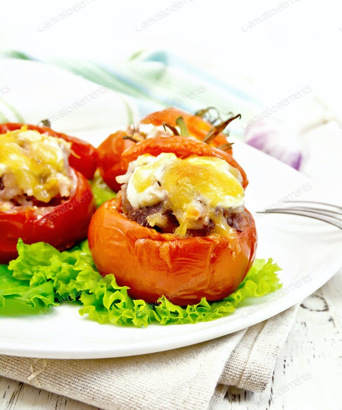 Tomatoes stuffed with rice and meat with lettuce in plate on boa