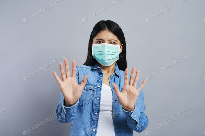 Frightened Asian woman in surgical mask