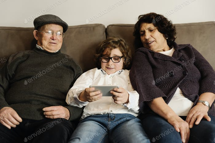 Grandparents and grandson using mobile.