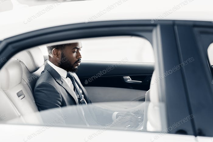 Busy day. Businessman sitting on back seat of car
