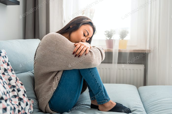 Unhappy lonely depressed asian woman on sofa at home