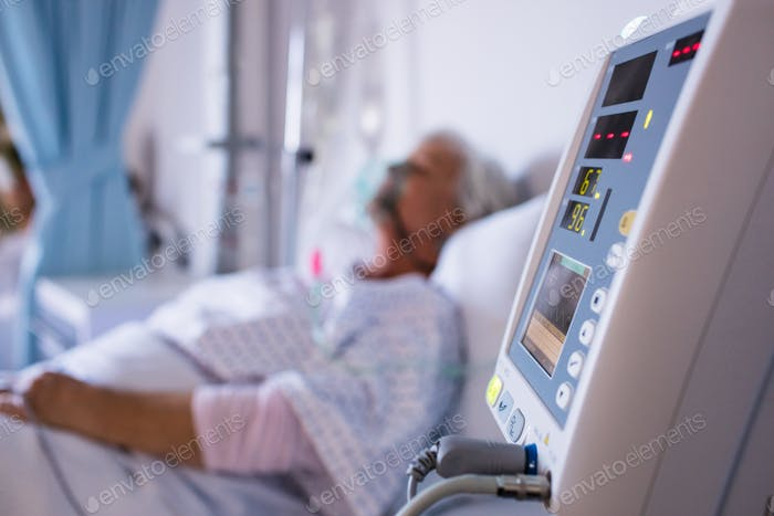 Close-up of vital signs monitor with senior patient in the background