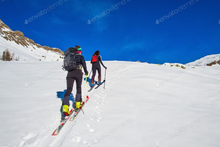 Ski mountaineering two girl uphill towards a mountain