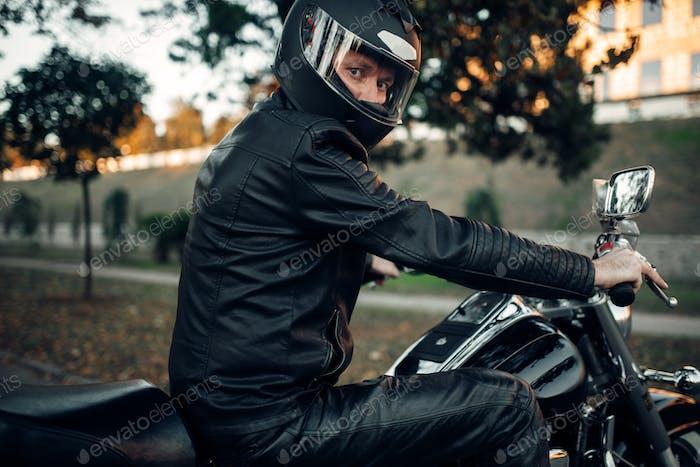 Biker in helmet poses on classical chopper