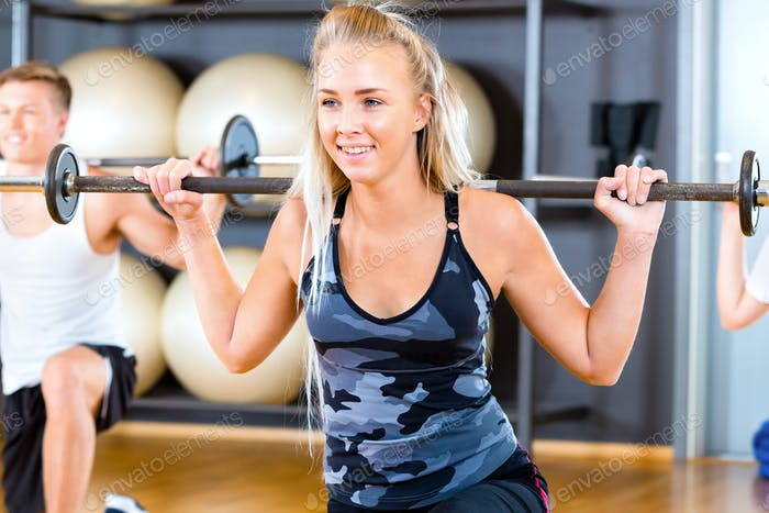 Close-up of Young Woman Lifting Barbell Rod With Friends In Gym