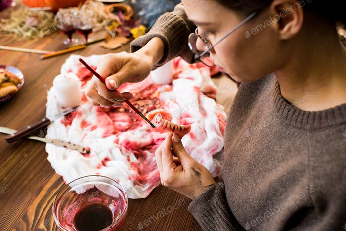 Painting toy teeth with paint of blood color