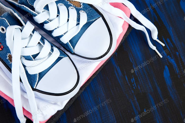Flat lay of female sneakers shoes and tee