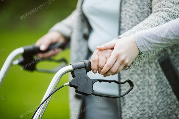 Senior Frau mit Walker während des Spaziergangs im Park der modernen Pflegeheim