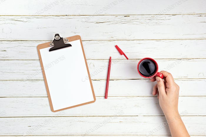 Hand holding red coffee cup, blank notepad and pen on white wooden background