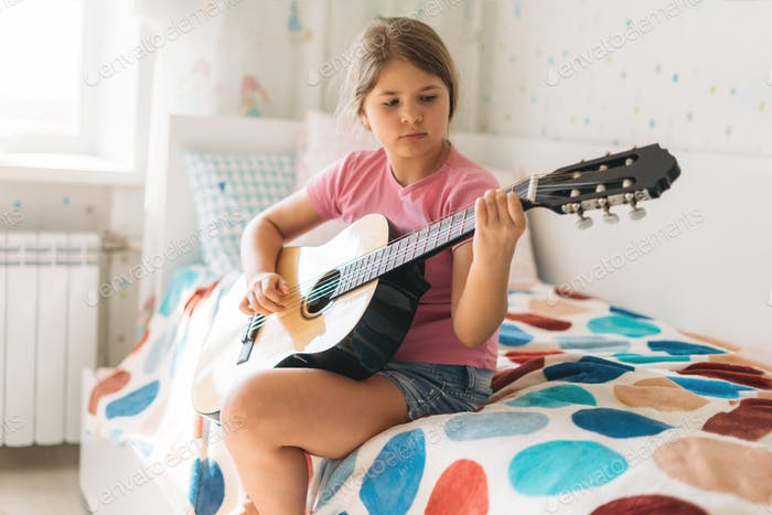 Cute tween girl in pink t-shirt play guitar sit on bed