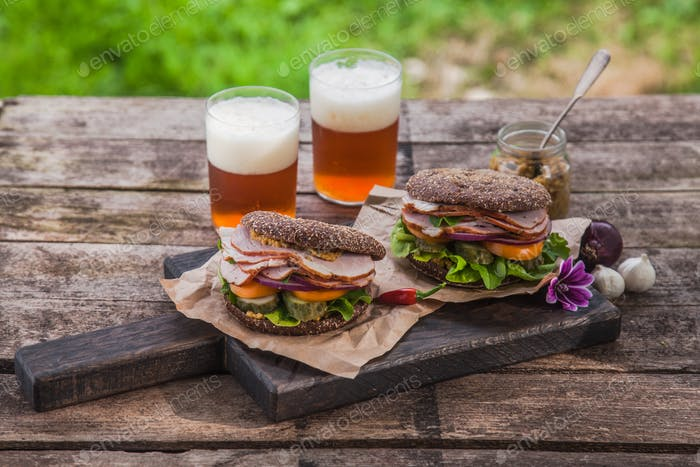 Homemade sandwich with ham and a glass of beer on an old background