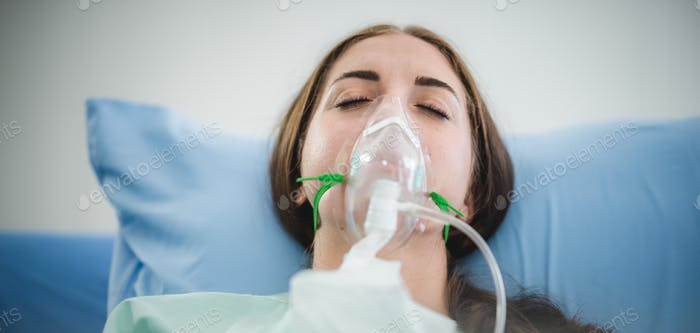 young woman patient receiving oxygen mask lying on a hospital bed, concept of medical and patient
