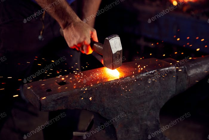 Close Up Of Male Blacksmith Hammering Metalwork On Anvil With Sparks