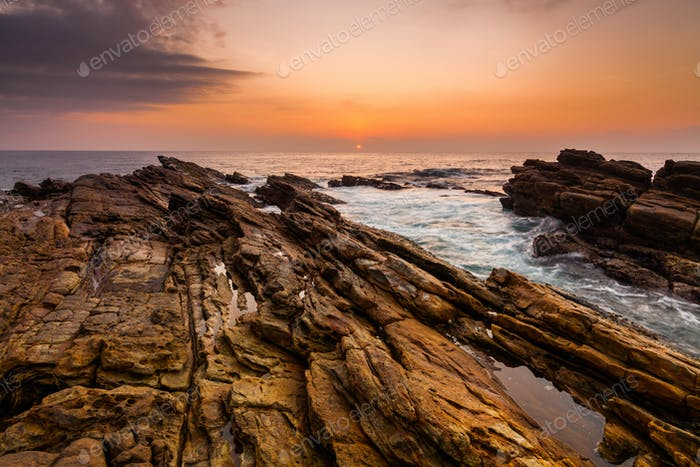 Sunset on the rocky shore of a tropical island