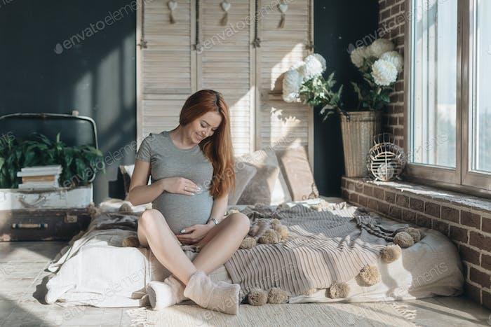 Schwangere berührt und schaut auf ihren Bauch