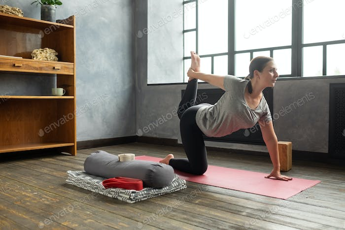 Young woman working out at home doing yoga, pilates balancing exercise