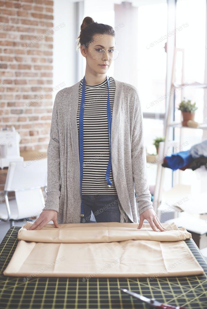 Female dressmaker measuring textile material