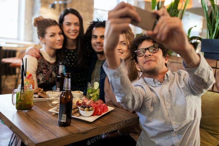 Freunde nehmen Selfie per Smartphone an der Bar oder im Café