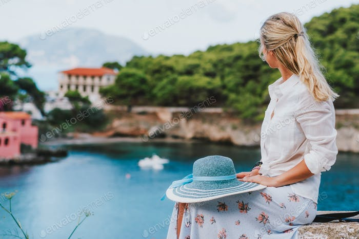 Beautiful blond woman holding blue sunhat sitting and enjoying blue bay of colorful tranquil village