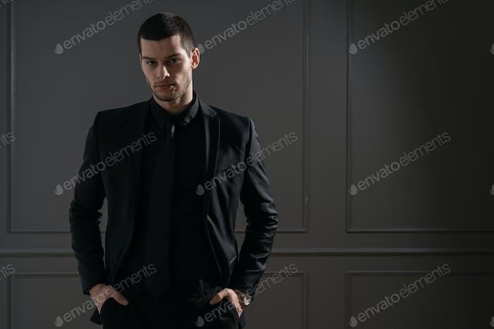 Junge gutaussehende Geschäftsmann in schwarzes Hemd und schwarzen Anzug