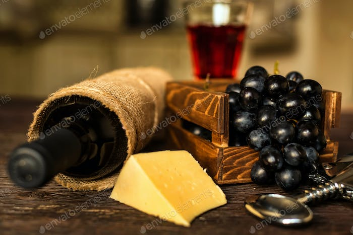 Glass of red wine with bottle, cheese and grapes