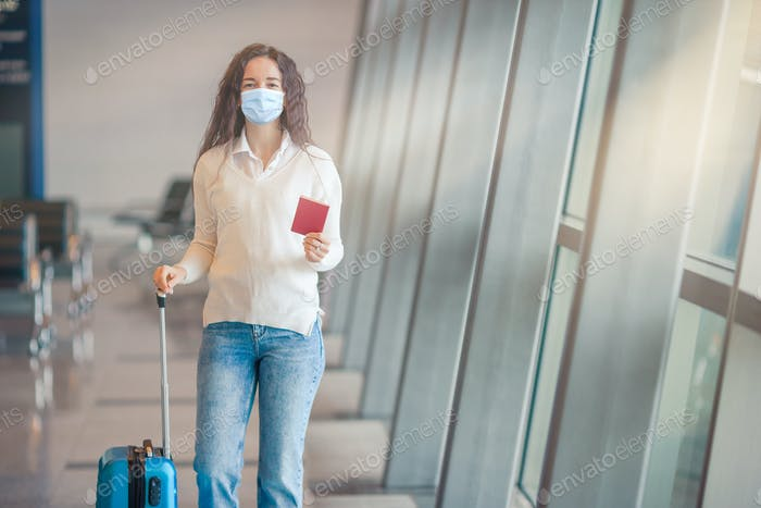 Young woman with luggage in international airport. Airline passenger in an airport lounge waiting