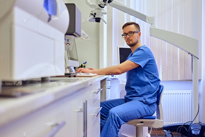 Male dentist in a room with medical equipment on background.