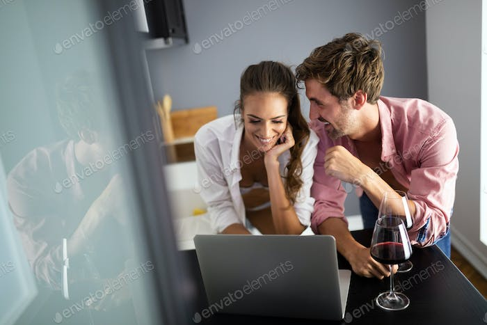 Young couple relaxing at home with laptop. Love,happiness,people and fun concept