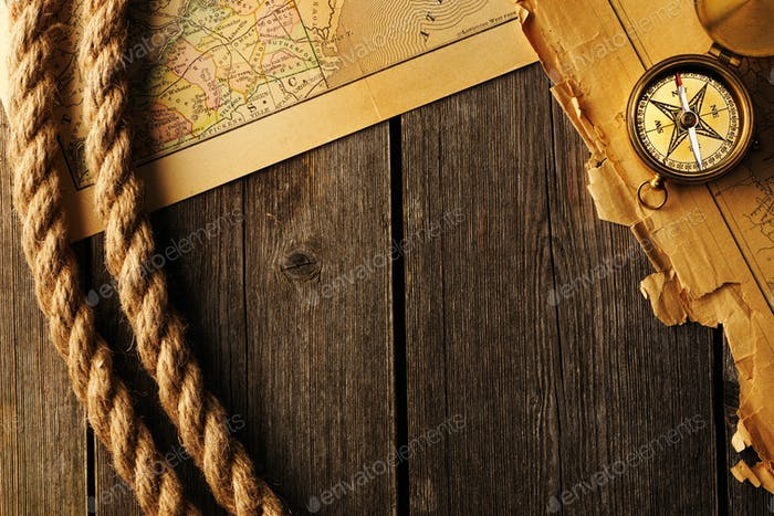 Antique compass and rope over old map