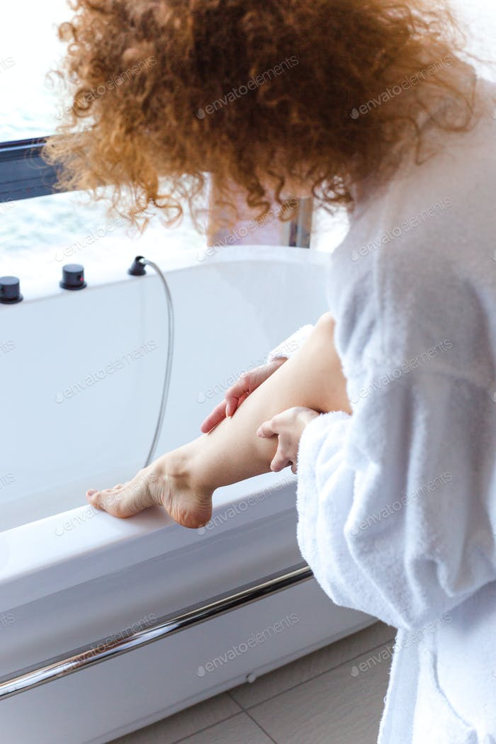 Curly woman in white bathrobe put her leg on bathtub