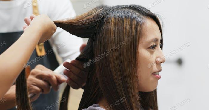 Stylist dries client hair in salon