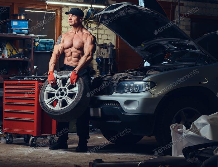 Ein Mann, der das Rad eines Autos repariert.