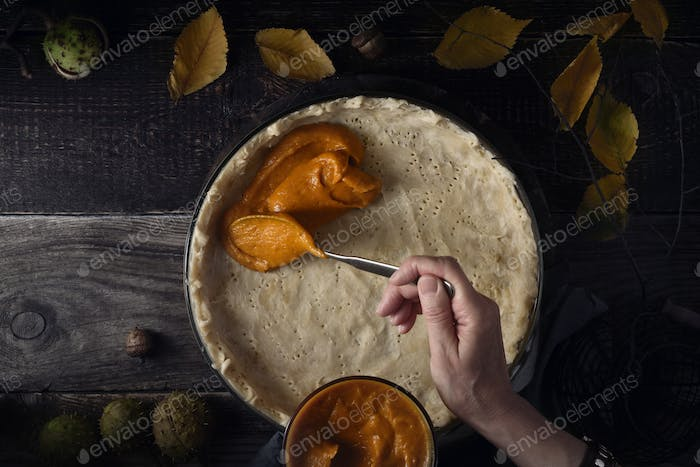 Putting  pumpkin puree on the dough for pumpkin pie horizontal