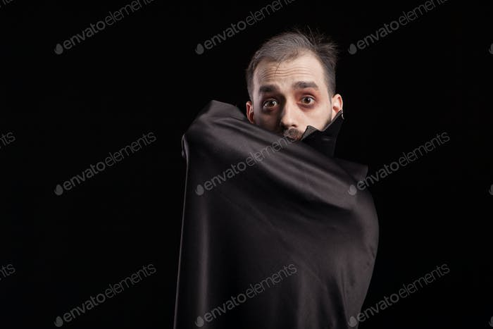 Man dressed up in dracula costume for halloween hiding behing his cape
