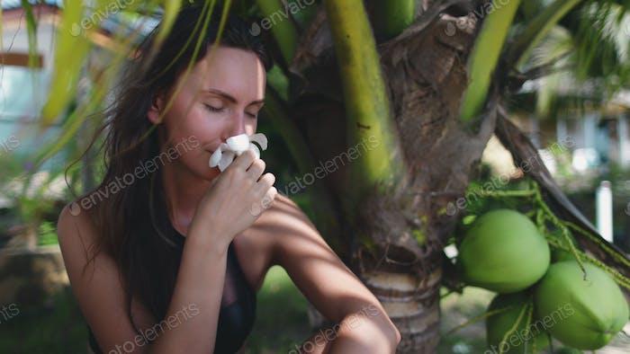 beautiful carefree woman sit under palm tree leaf