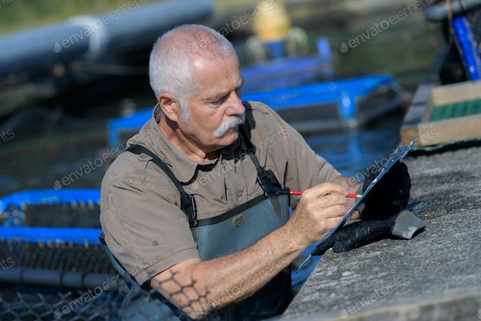 senior man managing his fish farm