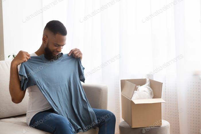 African american man tries on a tshirt received from online store