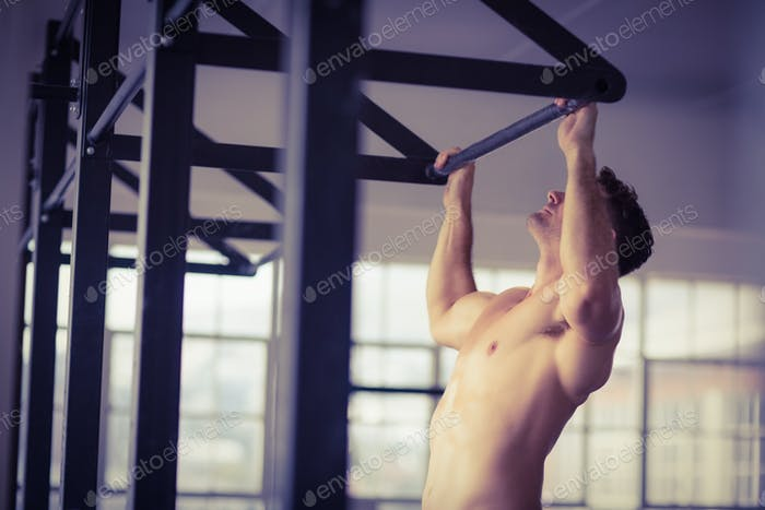 Muscular man lifting himself up and down in crossfit gym