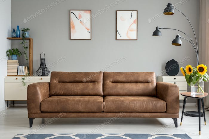 Leather sofa next to table with sunflowers in grey living room i