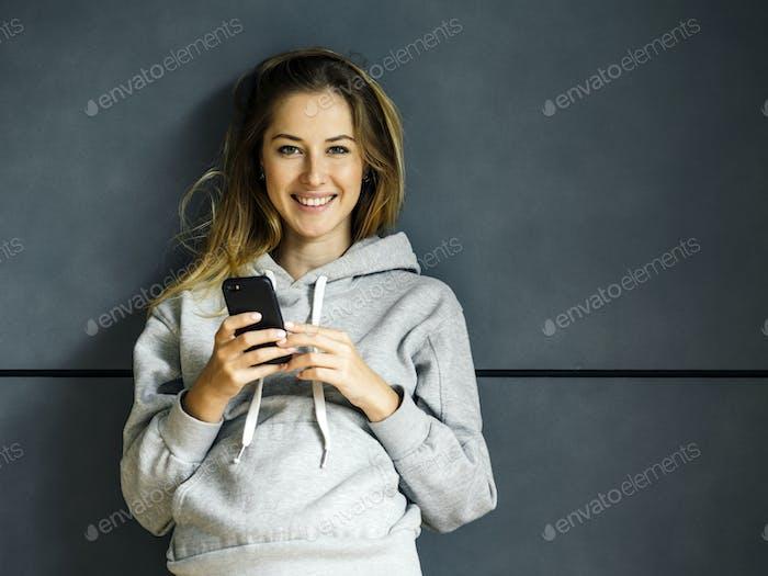 Lächelnde junge Frau mit ihrem Handy