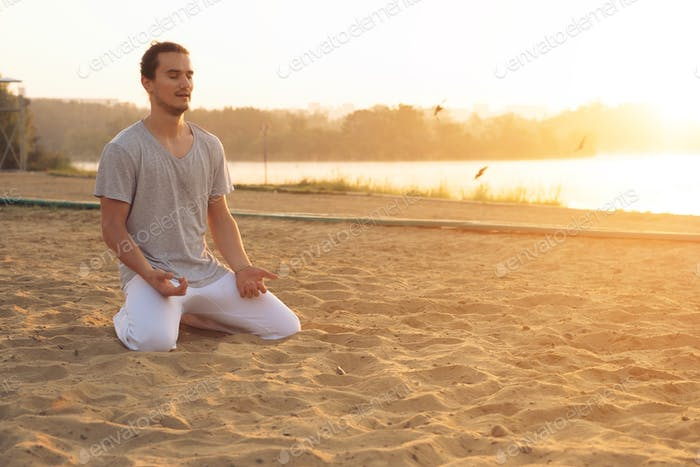 Young attractive man meditating on the beach in the park